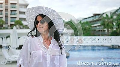 Χαμογελαστή τουρίστρια με καπέλο και γυαλιά ηλίου που περπατά κοντά σε πισίνα θαυμάζοντας το πολυτελές θέρετρο φιλμ μικρού μήκους