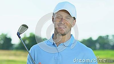 Χαμογελαστός παίκτης του γκολφ που κρατά σιδερένιο κλαμπ που ποζάρει στην κάμερα, χόμπι, ψυχαγωγία απόθεμα βίντεο