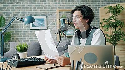 Χαμογελαστό αγόρι που διαβάζει μεγαλοφώνως στο podcast ηχογράφησης του μικροφώνου στο μοντέρνο στούντιο απόθεμα βίντεο