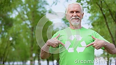 Χαμογελαστό ώριμο αρσενικό που δείχνει το σύμβολο ανακύκλωσης στο πράσινο μπλουζάκι, οικολογία απόθεμα βίντεο