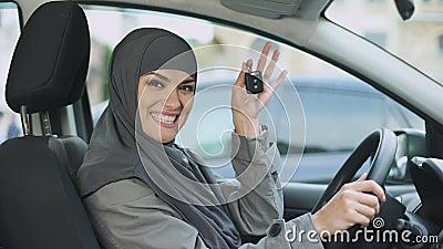 Χαμογελώντας κυρία στο hijab που παρουσιάζει κλειδιά αυτοκινήτων στη κάμερα που αγοράζει τη νέα αυτόματη άδεια οδήγησης απόθεμα βίντεο