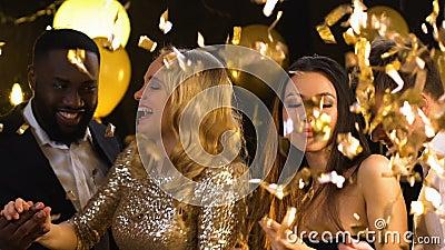 Χαμογελώντας πολυφυλετικά ζεύγη που χορεύουν στο κόμμα κάτω από το μειωμένο κομφετί, ευτυχία απόθεμα βίντεο
