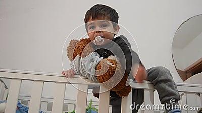 Χαριτωμένα δύο χρονών που κρατούν teddy αντέχουν ντυμένος στο κοστούμι σωμάτων μωρών και κλήση mom για να τον πάρουν από την κούν φιλμ μικρού μήκους
