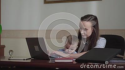 Χαριτωμένη επιχειρηματίας πορτρέτου με το μωρό και φορητός προσωπικός υπολογιστής που λειτουργεί στο γραφείο απόθεμα βίντεο
