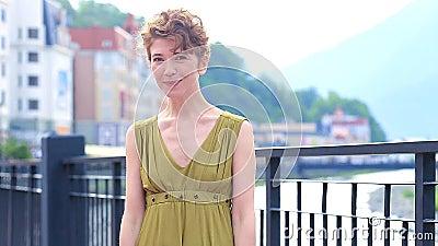 Χαριτωμένη καλή νέα γυναίκα μέσα σε ένα φόρεμα που στέκεται και που στέλνει το φιλί πέρα από τις πόλεις υποβάθρου Συγκινήσεις, ευ φιλμ μικρού μήκους
