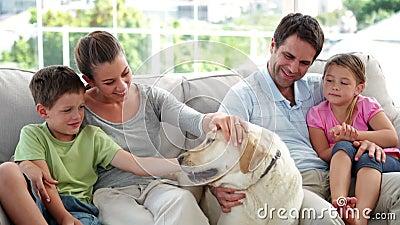 Χαριτωμένη οικογενειακή χαλάρωση μαζί στον καναπέ με το σκυλί του Λαμπραντόρ τους απόθεμα βίντεο