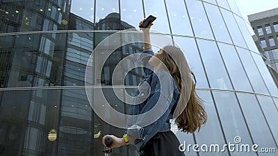 Χαριτωμένος τουρίστας που παίρνει τις εικόνες του φουτουριστικού εμπορικού κέντρου με τη κάμερα smartphone απόθεμα βίντεο