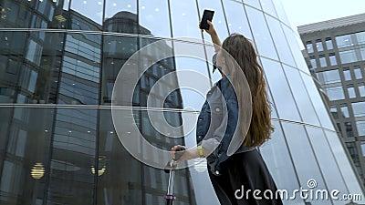 Χαριτωμένος τουρίστας που παίρνει τις εικόνες του φουτουριστικού εμπορικού κέντρου με τη κάμερα smartphone φιλμ μικρού μήκους