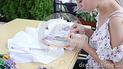 Χαριτωμένο κορίτσι στο τραπέζι που ραφτεί με βελόνα κεντητικό, χόμπι, χειροτεχνία απόθεμα βίντεο
