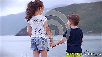 Χαρούμενα οικογενειακά παιδιά αγόρι και κορίτσι που κρατιούνται χέρι χέρι χέρι παιδιά που βλέπουν τη θάλασσα στον ωκεανό του ηλιο φιλμ μικρού μήκους