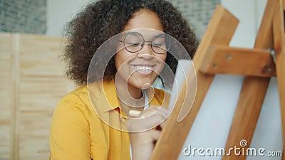 Χαρούμενη αφρικανή Αμερικανίδα έφηβη ζωγραφιά στο σπίτι χαμογελαστή χόμπι απόθεμα βίντεο