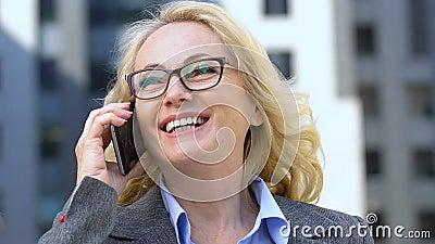 Χαρούμενη γυναίκα υπάλληλος μιλάει στο κινητό τηλέφωνο, αποτελεσματικές διαπραγματεύσεις για κινητά φιλμ μικρού μήκους