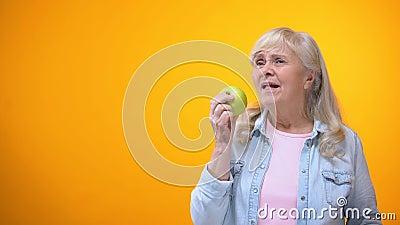 Χαρούμενη ηλικίας γυναίκα που απολαμβάνει το γούστο του φρέσκου τριζάτου μήλου, στοματική φροντίδα, orthodontics απόθεμα βίντεο