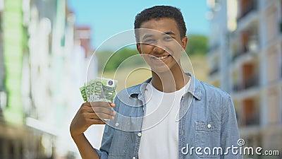 Χαρούμενος νεαρός άνδρας μικτής φυλής που δείχνει τσούρμο ευρώ και χαμογελά, χρηματοδότηση πρώτου μισθού φιλμ μικρού μήκους