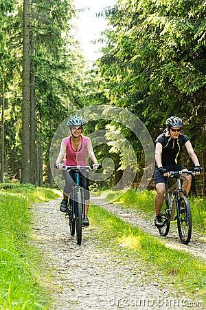 Χαρούμενο ζεύγος ποδηλατών στα ξύλα