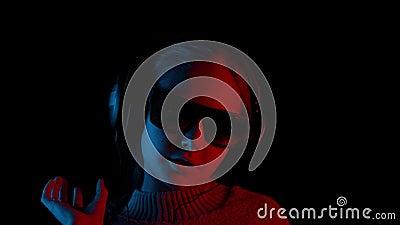 Χαρούμενο κορίτσι με ακουστικά και γυαλιά ηλίου που τραγουδάει στο σκοτάδι απόθεμα βίντεο