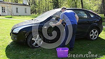 Χειρωνακτικός καθαρισμός πλυσίματος αυτοκινήτων χεριών με τον αφρό και το σφουγγάρι σε υπαίθριο απόθεμα βίντεο