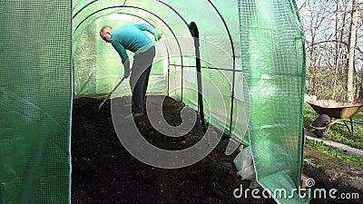 Χώμα επιπέδων ατόμων κηπουρών με raker το εργαλείο στο θερμοκήπιο 4K απόθεμα βίντεο