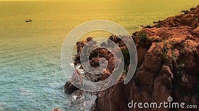 Ωκεάνια επιφάνεια νερού και σκόπελος βράχου παράκτιος στο σούρουπο φιλμ μικρού μήκους