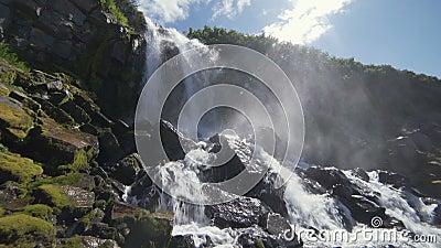Όμορφη άποψη του καταρράκτη Οι υψηλοί απότομοι βράχοι που καλύπτονται με το πράσινο βρύο, ο ήλιος λάμπουν στο πλαίσιο, πτώση πτώσ απόθεμα βίντεο
