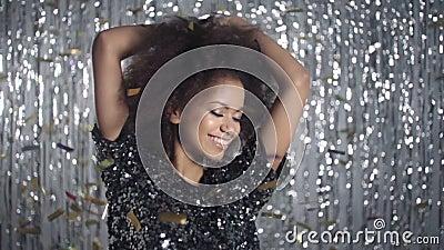Όμορφη αμερικανική γυναίκα afro που χορεύει μεταξύ του χρυσού κομφετί, σε αργή κίνηση φιλμ μικρού μήκους