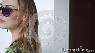 Όμορφη γυναίκα γοητείας που φορούν το μαύρο swimwear, floral μακρύ πουκάμισο και γυαλιά ηλίου που περπατούν έξω του χώρου ανάπαυσ απόθεμα βίντεο