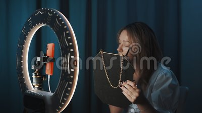 Όμορφη γυναίκα εφαρμόζει καλλυντικά μπροστά από το φως των δαχτύλων, με ροή στο διαδίκτυο απόθεμα βίντεο