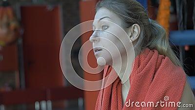 Όμορφη γυναίκα που σκουπίζει το λαιμό της με μια πετσέτα μετά από το workout στη γυμναστική απόθεμα βίντεο