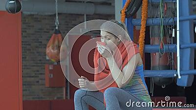 Όμορφη γυναίκα που σκουπίζει το λαιμό της με μια πετσέτα μετά από το workout στη γυμναστική φιλμ μικρού μήκους