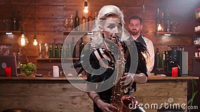 Όμορφη γυναίκα στο μαύρο σκηνικό κοστούμι που παίζει μια μελωδία στο saxophone απόθεμα βίντεο