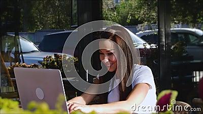 Όμορφη ηλιόλουστη μέρα Νεαρή γυναίκα πίνει τον πρωινό καφέ της σε καφετέρια, κάνοντας την αγορά εύκολη στο διαδίκτυο απόθεμα βίντεο