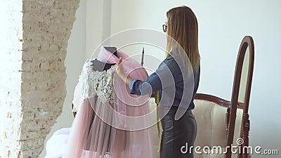 Όμορφη ξανθιά με ραφή στο στούντιο ραφής, δουλεύει με ύφασμα κοντά στην κούκλα η διαδικασία δημιουργίας μοντέλων γυναικών`s φιλμ μικρού μήκους