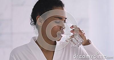 Όμορφη υγιής αφρικανή γυναίκα που πίνει φρέσκο μεταλλικό νερό το πρωί απόθεμα βίντεο