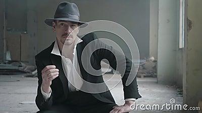 Όμορφο βέβαιο άτομο πορτρέτου σε ένα καπέλο που γυρίζει το νόμισμα στα δάχτυλα που κάθονται σε ένα εγκαταλειμμένο κτήριο Το κεφάλ απόθεμα βίντεο