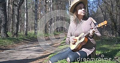 Όμορφο νεαρό κορίτσι με ukulele στη φύση απόθεμα βίντεο