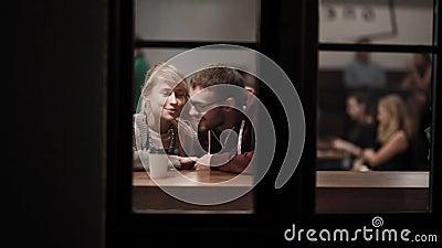 Όψη μέσω του παραθύρου Νέα όμορφη συνεδρίαση ζευγών στον καφέ και ομιλία Ρομαντική ημερομηνία μέσα κεντρικός το βράδυ απόθεμα βίντεο