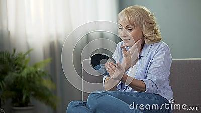 Ώριμη γυναίκα που εξετάζει έναν καθρέφτη χεριών, που απολαμβάνει την αντανάκλαση Καλλυντικά αντι-ηλικίας απόθεμα βίντεο