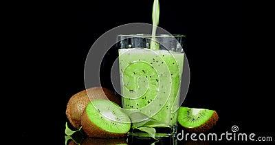 Ώριμος χυμός kiwi χτυριασμένος σε ποτήρι απόθεμα βίντεο