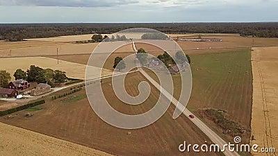 Автомобиль двигая дальше дорогу сельской местности сельскую среди пшеничных полей и сельских домов хлопьев видеоматериал