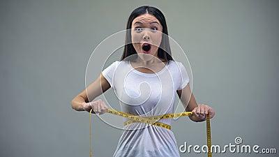 Азиатская женщина измеряя ее талию, удовлетворяемую с результатами тренировки и диеты, пригонка сток-видео
