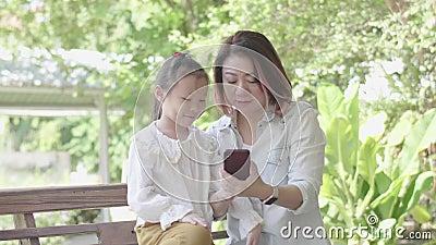 Азиатская жизнерадостная мать с дочерью, сидящей в саду акции видеоматериалы