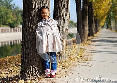 Азиатская маленькая девочка в осени