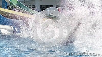 Активный человек скользит по склону в аквапарке, окруженном брызгами и медленным движением пузыря акции видеоматериалы