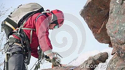 Альпинист человека в красных костюме и оборудовании, на его коленях, взбирается гора полагаясь на оси льда сток-видео