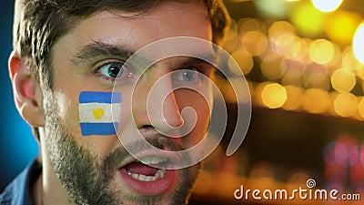 Аргентинский футбольный болельщик с флагом на щеке радуясь любимая победа команды акции видеоматериалы