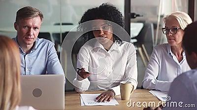 Афро-американская коммерсантка говоря с клиентами на разнообразных переговорах группы акции видеоматериалы
