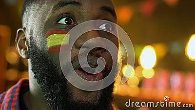 Афро-американская мужская победа футбольной команды ликования вентилятора, испанский флаг на щеке сток-видео