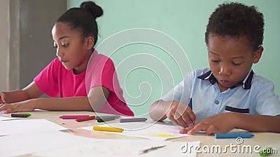Афро-американские дети уча как нарисовать с crayon на таблице сток-видео