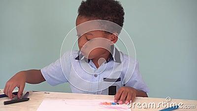 Афро-американский мальчик уча как нарисовать с crayon на таблице сток-видео