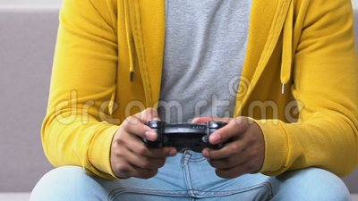 Афро-американский парень ослабляя на кресле, пристрастившийся к игре видеоигр, отдыха акции видеоматериалы